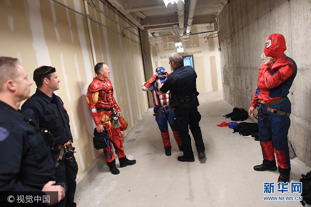 當地時間2017年10月17日,美國科羅拉多州奧羅拉,當地警察裝扮成超級英雄,從兒童醫院的天臺上從天而降為病童們送驚喜。***_***AURORA, CO - OCTOBER 17: Aurora Police Strategic Response Team member Paul Davis helps fellow officer Jeff Jacobs dress up as the superhero Captain America on October 17, 2017 in Aurora, Colorado. Members of the Aurora Police Strategic Response Team rappeled from the rooftop of Childrens Hospital Colorado, dressed as superheroes, to surprise patients, families and staff. (Photo by RJ Sangosti/The Denver Post via Getty Images)