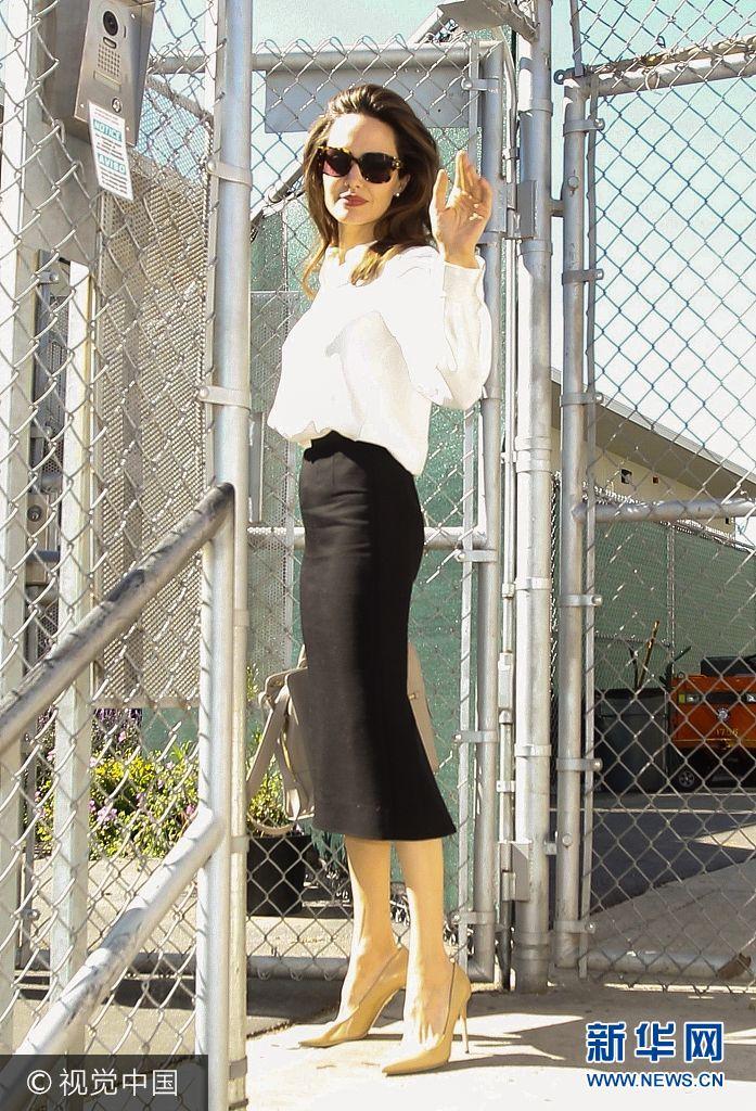 """當地時間2017年10月26日,美國洛杉磯,安吉麗娜·朱莉(ngelina Jolie)現身新片《他們先殺了我父親》(First They Killed My Father)的拍攝現場。安吉麗娜·朱莉身穿OL風黑白套裝現身氣場全開,攻氣十足,她在片場扶欄桿凹造型,回眸用""""鼻孔看人"""",霸氣側漏。(圖片來源:視覺中國)"""